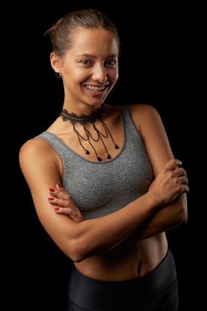Beautiful girl with braces stands with crossed arms. Isolated