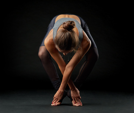 Yoga woman in bending pose on black background. Young adult Stock Photo