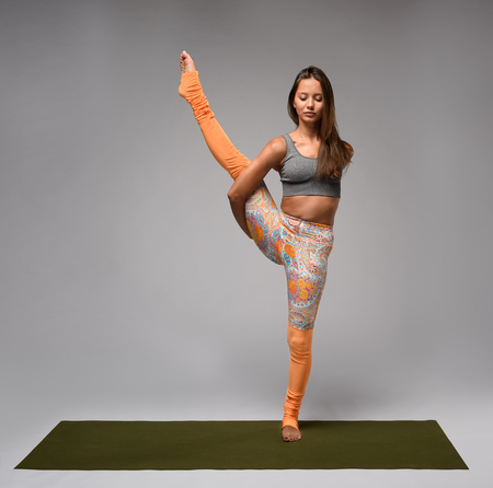 hasta: Pretty young woman doing yoga standing on one leg. Studio