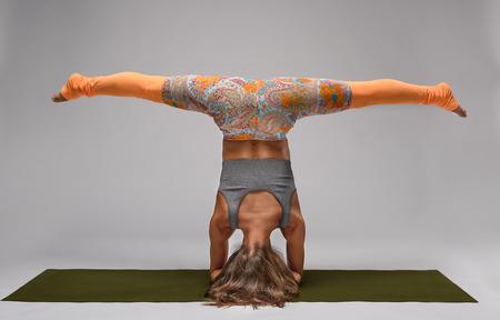 beine spreizen: Beautiful young girl standing on her head with her legs spread in yoga pose in studio