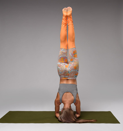 headstand: Young yoga woman standing on head in shirshasana. Back view Stock Photo