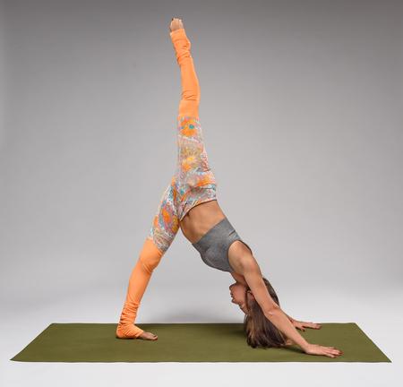 dog pose: Girl on yoga mat practicing in downward facing dog pose
