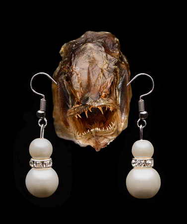 fas: Monster fish with pearl earrings on black background Stock Photo