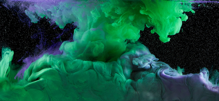 Art colorful ink mix in water on black background. Purple and green
