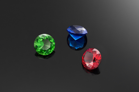 Three huge precious stones on black background. Round-cut ruby, emerald and sapphire. Jewelry. Stock fotó