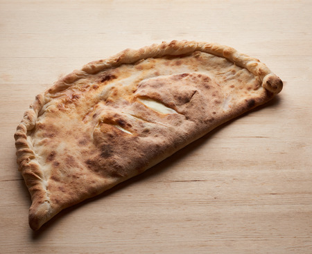 Calzone. Closed Italian pizza on wooden table. Tasty baked Stock Photo