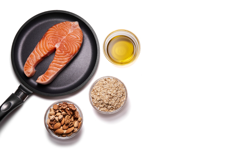 Salmon steak on frying pan and products for heart health. Isolated on white background. Bowls with olive oil nuts and cereals. Copyspace