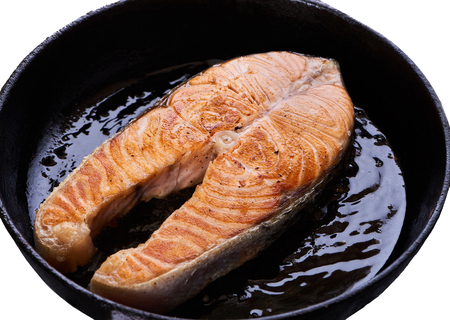Filete de salmón en sartén negra. Con aceite de pescado asado sabroso sobre fondo blanco. Foto de archivo