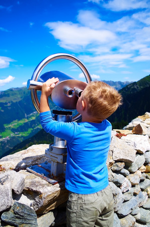 Little boy looking at the mountains through telescope photo