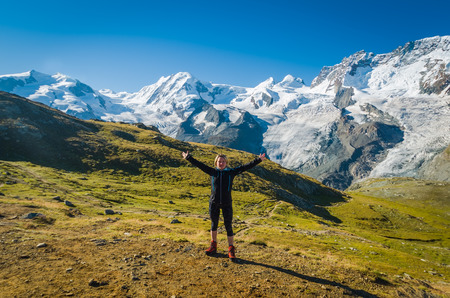 arms wide open: Woman with arms wide open standing in front of Monte rosa glacier Stock Photo