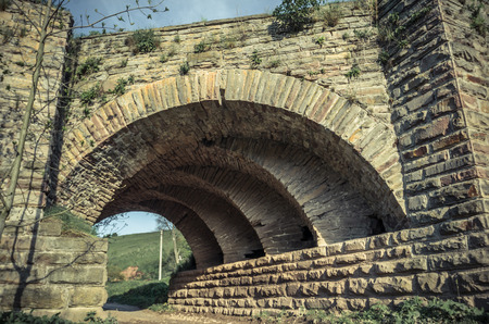 View of the arcs of the old historic stone bridge located in Ukraine Banco de Imagens