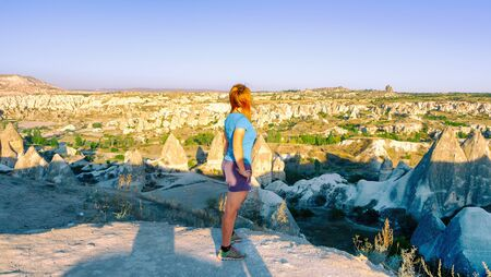 View from the back of a girl stands on a hill and looks at Goreme, Cappadocia in Turkey.