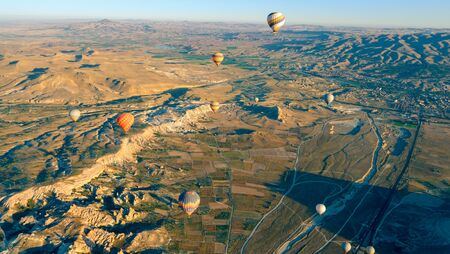 Aerial view of air balloon over fields, Cappadocia, Turkey. Aerial summer view from air balloon over road in Goreme, Cappadocia, Turkey. Aerial balloon over mountains at sunrise, Cappadocia, Turkey. 写真素材