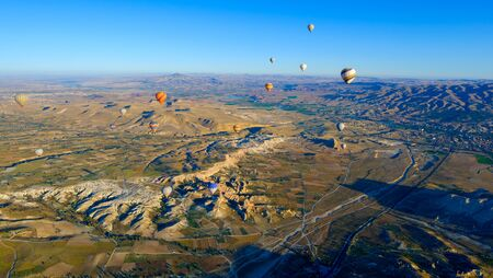 View of the colorful air balloon flying over rock formation and beautiful valley, Cappadocia, Turkey 写真素材