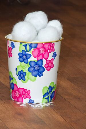 palle di neve: Bucket with faux snowballs placed on a wooden floor.