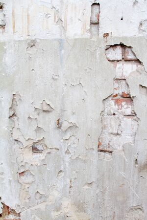 mess: Vintage background texture of old brick masonry on ancient cement with cracks with traces of old paint.