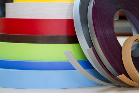 Multicolored bobbins of PVC edge and melanin for the manufacture of furniture. Lie pyramid.