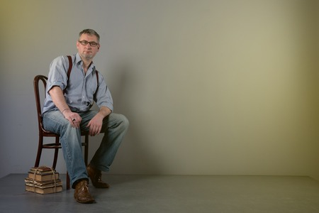 Writer with glasses and suspenders is thinking about his work Stock Photo