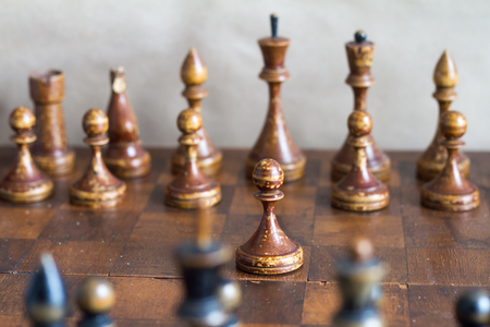 Vintage wooden chess pieces on an old chessboard. Stock Photo