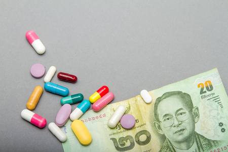 Medical pills in different colors and money. Stock Photo