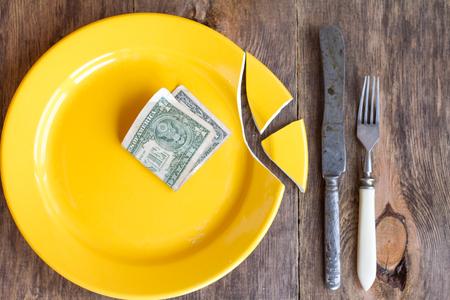 Broken plate and money. Stock Photo