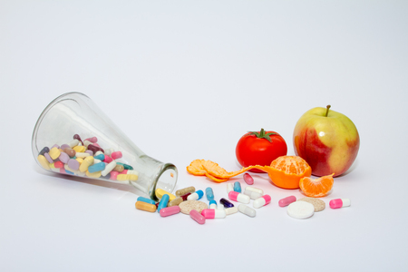 Colorful medical pills in a glass container on a white background.