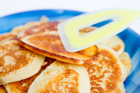 Ruddy freshly cooked pancakes lie on a blue plate on a white background.