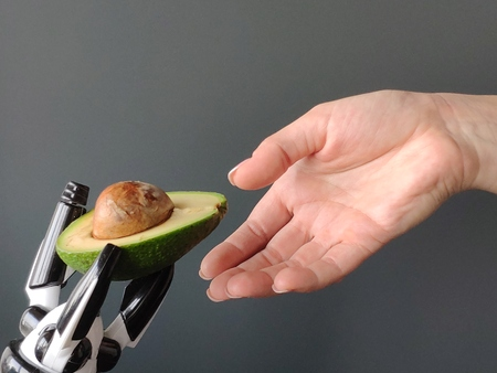 A robot's hand stretches an avocado into a young woman's hand, background or concept, free space for text.