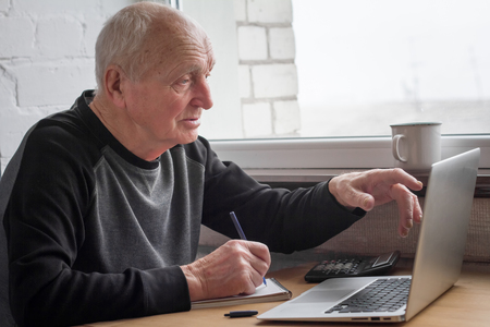 An old man points his finger at a laptop screen and takes notes in a notebook, selective focus, free space for text.