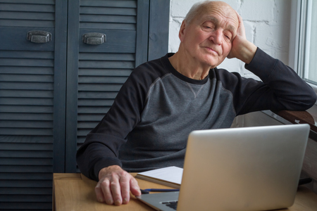 An elderly man is tired of looking at the screen of an open laptop, counting taxes, selective focus, free space for text.