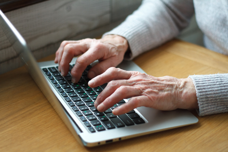 Mature female hands typing text on keyboard, senior elderly business woman working on laptop, old or middle aged lady using computer concept writing emails, communicating online, close up view. Imagens
