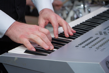 Beautiful mans hands on the keys of synthesizer, selected focus. Reklamní fotografie