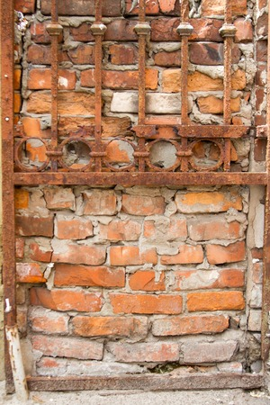 Rusty lattice on the background of an old red brick wall, background or concept, free space for text