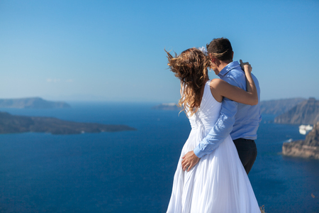 young couple honeymoon on the most romantic island Santorini, Greece, beautiful view of the sea and islands. Banco de Imagens - 120655813