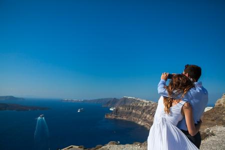 young couple honeymoon on the most romantic island Santorini, Greece, make a selfie on the background of Santorini.