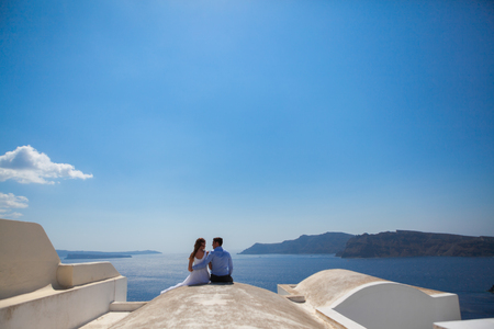 young couple honeymoon on the most romantic island Santorini, Greece, look at the beautiful view.