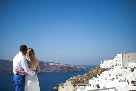 jong koppel zwanger op het meest romantische eiland Santorini, Griekenland, uitzicht op Santorini.