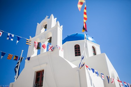 Oia town on Santorini island, Greece. Traditional and famous white houses and churches with blue domes over the Caldera, Aegean sea