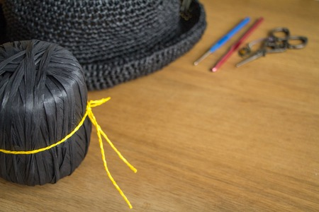 A skein of black yarn tied with a yellow thread next to a knitted black hat on a light wooden surface. Selective soft focus. Free space for text. Фото со стока
