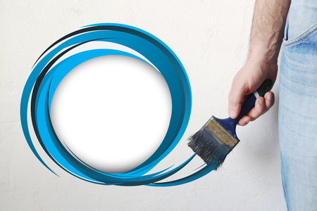 Mans hand holding paintbrush paint blue color drawn circle on white color wall, free space for your text, banner, copyspace, advertising, or your design. Imagens