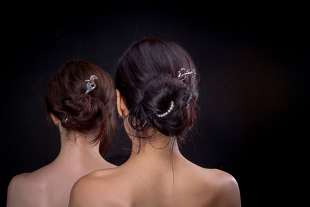 Two young women with vintage hairstyles and bare shoulders stand behind each other on a black background, the foreplay of love. Added a small grain, imitation of film photography.
