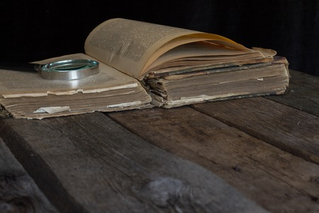 An old brown book and magnifying glass on rustic background. Close up. Vintage toning. Selective focus.