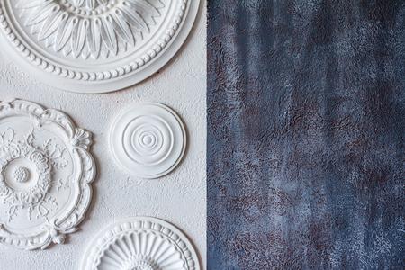Un fondo bicolor, yeso decorativo gris y una pared blanca con varios rosetones blancos en el techo.