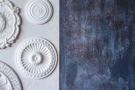 Dwukolorowe tło, szary tynk dekoracyjny i biała ściana z kilkoma białymi rozetami sufitowymi.