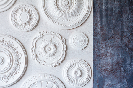 A two-color background, gray decorative plaster and a white wall with several white ceiling rosettes. Archivio Fotografico