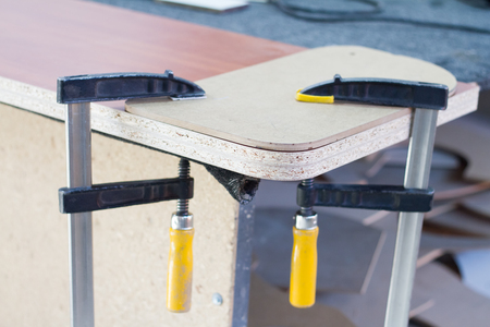 Making furniture in the process, gluing furniture panels for making furniture with clamps.