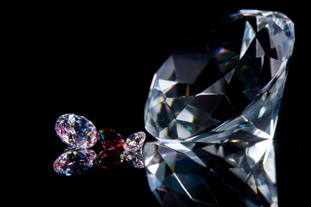 Huge diamond and several chic crystals on a deep black mirror surface, shimmer and sparkle, free space for text. 스톡 콘텐츠