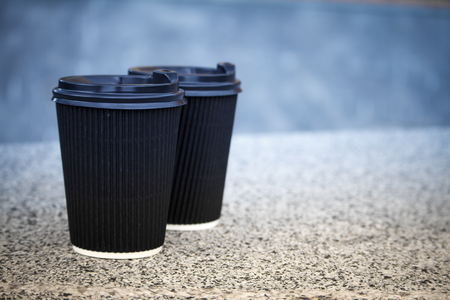 Two black disposable cups of coffee with lids are standing on the stone parapet, rest and a walk around the city, background or concept