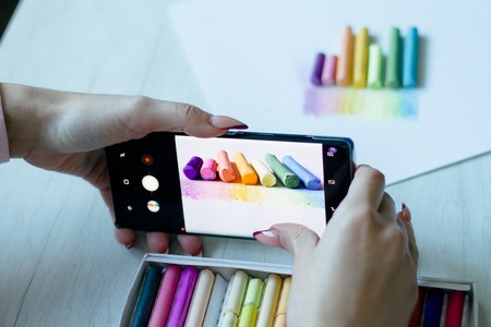 A girl takes on the smartphone multicolored chalks near a picture on a white sheet of paper, background or concept Archivio Fotografico