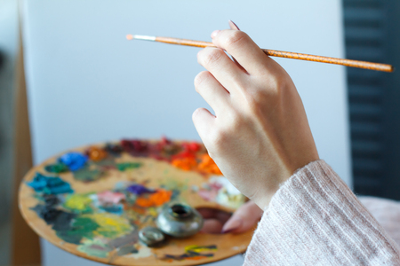 Close-up of female hands in a pink sweater holding a brush and a palette with multi-colored acrylic paints against a white canvas, selective focus Stok Fotoğraf